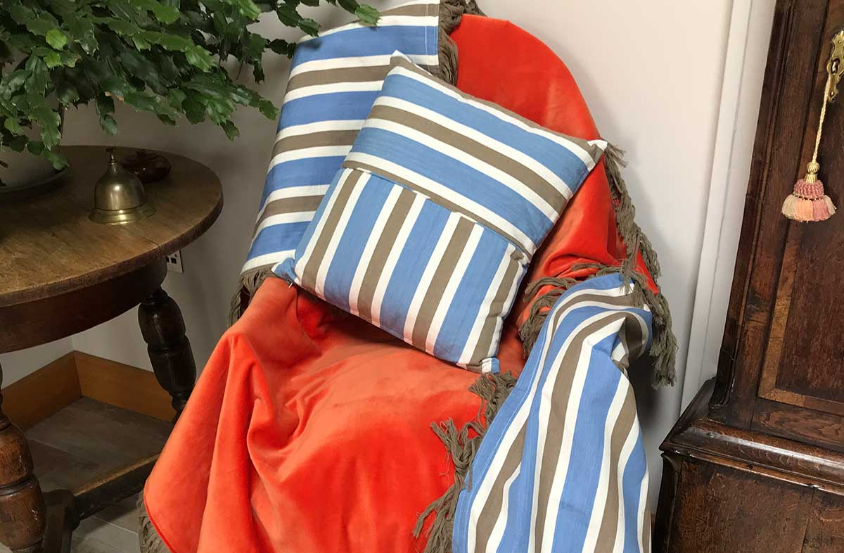 Reversible Orange Velvet Throw with Taupe Fringe and Blue, Beige and White Stripes on reverse